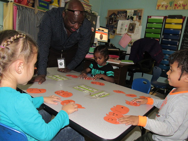 Staff photo by Cathy Spaulding<br /> Early Childhood Center teacher's assistant Robbie Anderson helps pupils — from left, Chloe Crafton, E'Thynn Mahone and Zadrian Hall — put together math puzzles. Anderson has been at ECC for about a year.