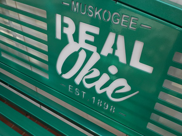 """Staff photo by Mike Elswick<br /> Newly installed downtown Muskogee benches reinforce the """"Real Okie"""" slogan."""