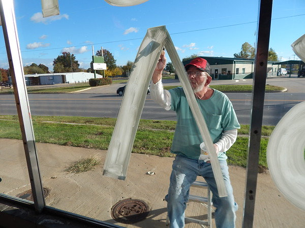 KENTON BROOKS/Muskogee Phoenix<br /> Rob Wyren of Weleetka paints a letter on the front window at Hamby TV & Appliance Warehouse on Thursday. Every Nov. 1, Wyren and his wife Lisa paint the windows with Christmas-related items.