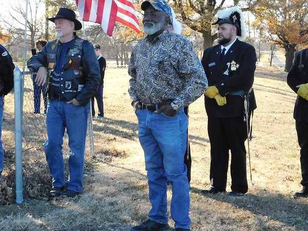 KENTON BROOKS/Muskogee Phoenix<br /> Jerry Love, center, stands and watches the Tuesday ceremony honoring the 27 veterans buried at Sandtown Cemetery, located northwest of Wagoner. Love maintains the grounds of the cemetery, is a U.S. Army veteran and was married at Sandtown Baptist Church. The church no longer exists, but maintaining the grounds and honoring the veterans is important to Love.
