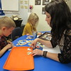 Staff photo by Cathy Spaulding<br /> Hilldale pre-kindergarten student Jenson Bearden looks for pictures to help him tell a story for his teacher, Sara Fletcher. The pictures were funded by a Hilldale Education Foundation grant.