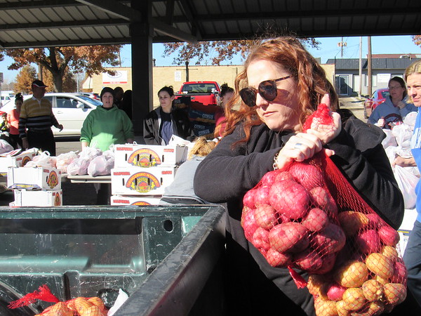 CATHY SPAULDING/Muskogee Phoenix<br /> Tammy Randazzo of the KI BOIS Supportive Services for Veterans Families loads a bag of potatoes in a pickup during a mobile pantry drive-through on Wednesday.