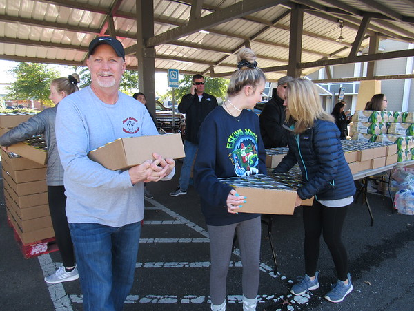 CATHY SPAULDING/Muskogee Phoenix<br /> Members of the Garner family, from left, Phillip Garner, Brylee Garner and Michelle Garner get ready to load boxes of cans into passing cars Wednesday as part of the Mobile Pantry for veterans.