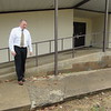 CATHY SPAULDING/Muskogee Phoenix<br /> Warner Schools Superintendent David Vinson shows a broken area on the elementary school sidewalk. A grant from the Tobacco Settlement Endowment Trust will help fund sidewalk repairs.