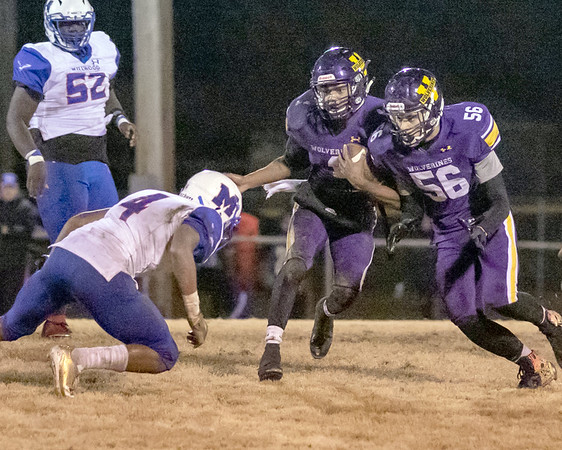SHANE KEETER/Special to the Phoenix<br /> Vian's Marcus Butler, right, blocks for teammate Javyn Wright, center, during the Wolverines' 47-16 Class 2A playoff win on Friday in Vian. Story in Sports.