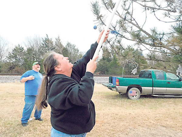 KENTON BROOKS/Muskogee Phoenix<br /> Wilma Hays strings Christmas lights and ornaments on one of the 34 trees that will be decorated on South Broadway in Checotah. Mike Key, Ward I city councilor, assists her. Key and Mayor Daniel Tarkington came up with the idea to decorate the trees in 2016 and has become an annual tradition in the McIntosh County city.