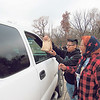 CATHY SPAULDING/Muskogee Phoenix<br /> Volunteers Brayan Barboza, left, and Liz Hanley hand a lunch bag to a motorist Saturday during the Hands Halting Hunger food giveaway at Mount Calvary Baptist Church.