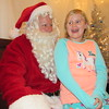 "Staff photo by Cathy Spaulding<br /> Lybbi Moore, 8, gives Santa a few gift-buying tips Friday. She visited Santa at Three Rivers Museum as part of ""The Polar Express Pajama Party."""