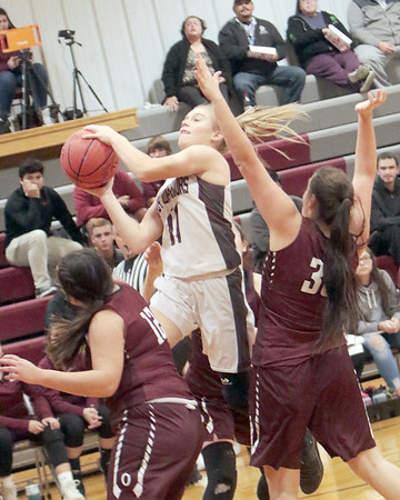 JOHN HASLER/Special to the Phoenix<br /> Webbers Falls' Samantha Shanks, center, drives for two between Oaks' Alyssa Cummings, left, and Harlie McKie during Monday's game.
