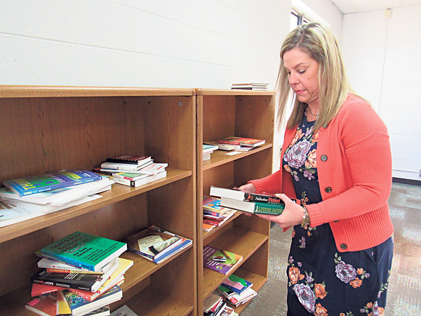 CATHY SPAULDING/Muskogee Phoenix<br /> Shannon Turner, Muskogee Public Schools executive director of federal programs, puts books on a shelf in her temporary office. Muskogee Public Schools temporarily moved administrative and enrollment services to the former Harris-Jobe Elementary School, 2809 N. Country Club Road. The district is remodeling its downtown Board of Education Service and Technology Center. MPS Communications and Marketing Director Steve Braun said officials hope the remodeling could be completed by the start of the 2020 school year. He said Board of Education meetings will be held at the school. There are no changes in telephone numbers, he said.
