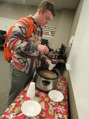 CATHY SPAULDING/Muskogee Phoenix<br /> Connors State College student Chase Bean of Stilwell fills up on Mexican hot chocolate at the CSC Muskogee campus library on Wednesday. Connors State College's Campus Recognition and Social Activities Committee set up hot chocolate and hot cider stations on Connors' Muskogee and Warner campuses on Wednesday. The Muskogee campus had stations at the library and Nursing & Allied Health Building.