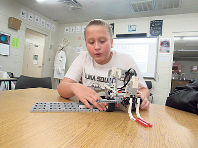 CATHY SPAULDING/Muskogee Phoenix Woodall seventh-grader Maddison Hamby explains how the Luna Squad's robot works.