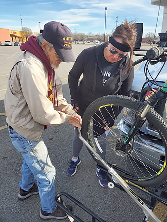 CHESLEY OXENDINE/Muskogee Phoenix<br /> Muskogee County Transit driver Butch Smith helps cyclist Kristin Janisch load her bike onto a new rack affixed to the front of an MCT bus.