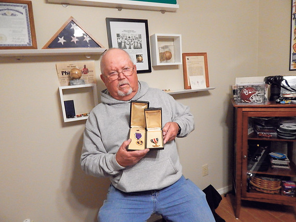KENTON BROOKS/Muskogee Phoenix<br /> Mark Downing shows two of his brother's medals he received in the Marine Corps. The Purple Heart is on the left, and the Silver Star is on the right.
