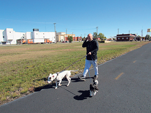 CATHY SPAULDING/Muskogee Phoenix<br /> Jason Puckett walks his dogs along Centennial Trail near the Oklahoma Music Hall of Fame on Thursday afternoon. Scout is a white pit bull mix and Sammy is a shih tzu.