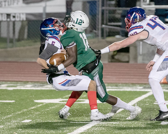 SHANE KEETER/Special to the Phoenix<br /> Muskogee's Caleb Webb, center, breaks through the Bixby's offensive to tackle Bixby quarterback Mason Williams, left, during the Roughers 51-7 loss to the Spartans on Friday on Creek Nation Field at Indian Bowl. Story in Sports.