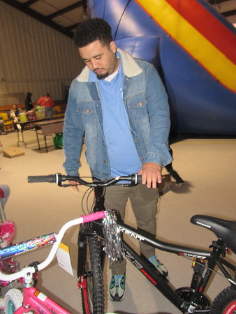 CATHY SPAULDING/Muskogee Phoenix<br /> Salvation Army Youth and Evangelism Outreach Director Chris Reeder straightens a bicycle during a children's party Wednesday at the Salvation Army.
