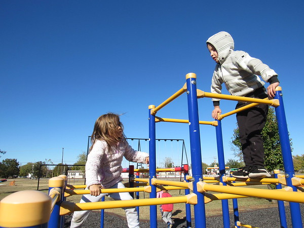 CATHY SPAULDING/Muskogee Phoenix<br /> Daphnee Custer, 5, and Luke Tucker, 7, climb a jungle gym at Okay Mustang Park. The park was dedicated Saturday.