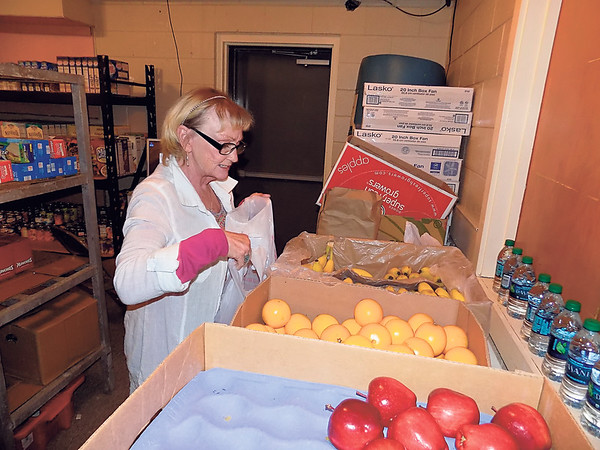Staff photo by Mike Elswick<br /> Muskogee Salvation Army volunteer Judy Bruton bags up fruit Friday as part of a new program focused on getting fresh vegetables and fruits in the homes of low-income county residents, especially those households with children and seniors. The free program will be held from 8 a.m. to 4 p.m. Fridays at 700 Independence St.