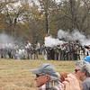 Staff photo by Cathy Spaulding<br /> Visitors with smartphones and cameras watch Confederate soldiers resist Union advances Saturday during a Battle of Honey Springs re-enactment. Another re-enactment is at 1 p.m. today.