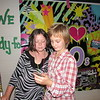 CATHY SPAULDING/Muskogee Phoenix<br /> Whittier Elementary fifth-graders Tenasi Ballard, left and Julia Boggs look at a picture Julia just shot during a Monday dance. Students wore 1980s garb and danced during the school's annual '80s for Alzheimer's Dance. The dance raised money for the Alzheimer's Association.