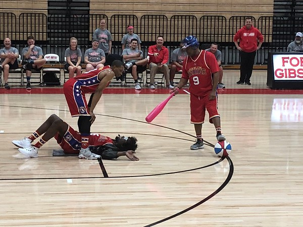 CHESLEY OXENDINE/Muskogee Phoenix<br /> From left: Harlem Wizards Devon Curry, Lloyd Clinton and Arnold Bernard halt Saturday night's Fort Gibson Basketball Booster Club fundraiser Fort Gibson basketball game for a comedy routine.