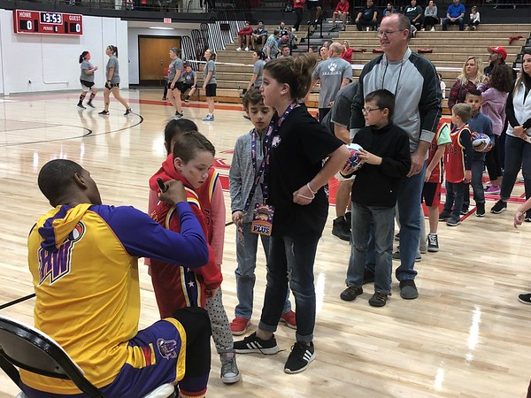 CHESLEY OXENDINE/Muskogee Phoenix<br /> Kids and parents line up to have gear autographed by the Harlem Wizards ahead of their game against the Fort Gibson Basketball Booster Club on Saturday night.