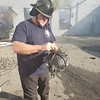 CHESLEY OXENDINE/Muskogee Phoenix<br /> Wagoner Fire Department Driver Jimmy Cagle shows the remnants of his helmet after fighting a fire that destroyed D&J's Auto Clinic in Wagoner on Tuesday.