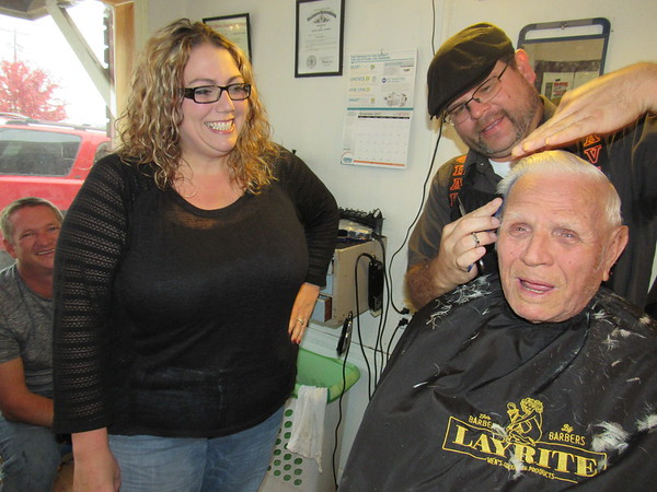 Staff photo by Cathy Spaulding<br /> New Chamber of Commerce Executive Director Jessica Fowler visits with barber Trey Reed as Reed cuts Leo Fox's hair. Fowler has busy weeks ahead as director.