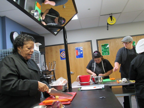 Staff photo by Cathy Spaulding<br /> Indian Capital Technology Center culinary arts teacher Georgiann Belton shows a safe, effective way to cut shoestring potatoes. The potatoes will be served at Belton's retirement reception on Thursday.