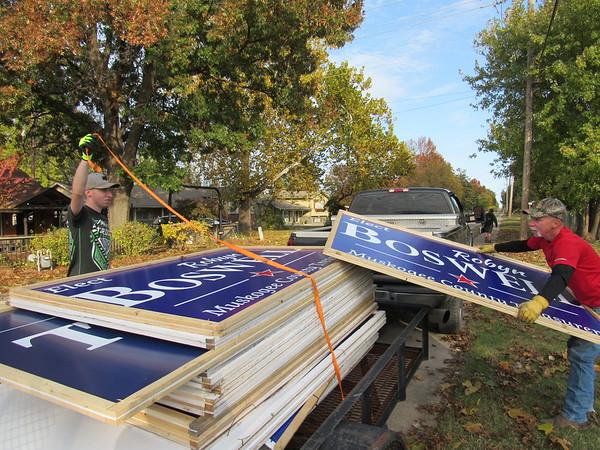 CATHY SPAULDING/Muskogee Phoenix<br /> Joshua Harmon, left, holds a securing rope while Don Harmon loads an Elect Boswell sign on a trailer Wednesday afternoon. Don Harmon spent Wednesday taking down campaign signs for his sister, Robyn Boswell, who won the race for Muskogee County treasurer the night before. Harmon said he's picking up 75 signs a day. He said they had put up about 1,200 large and small signs before the election.
