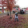 CATHY SPAULDING/Muskogee Phoenix<br /> Jeremiah Johnson, 9, carries an American flag across fallen leaves while helping set up flags at Fort Gibson's Centennial Park on Thursday. Youngsters, Fort Gibson High School football players and other volunteers put up more than 500 American flags around Fort Gibson's Centennial Park, along part of U.S. 62 and along the Trail of Honor on Willey Road to Cemetery Road to Fort Gibson National Cemetery. The flags will be up until Tuesday. Frank Gladd American Legion Post 20 and Trail of Honor Flags Inc. host the display.