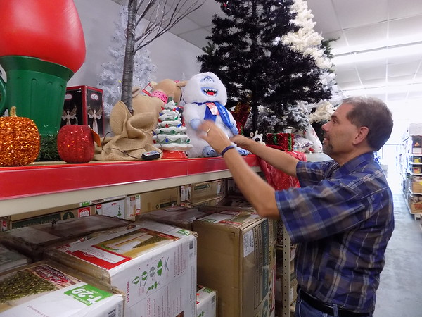Staff photo by Mike Elswick<br /> Lee Smith, Hwy 69 Outlet East Annex manager, is seen working at arranging holiday items on the shelves of the recently opened store. By mid-December the grocery component to the new location should be open next door in the former Save-A-Lot grocery store, according to Bill Johnson, owner.