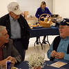 Staff photo by Mike Elswick<br /> Greg Schuler, left, Stan Martin, standing, and Mark Yanz, right visit during the beginning of Wednesday night's banquet honoring veterans hosted by the Greater Muskogee Area Chamber of Commerce. All three men are Navy veterans.