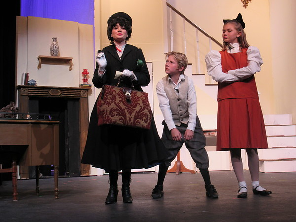 """Staff photo by Cathy Spaulding<br /> The Banks children (Tommy Woodburn, center, and Isabella Locke) size up their new nanny, Mary Poppins (Jessica Holloway) in a scene from the Muskogee Little Theatre production of """"Mary Poppins."""""""