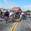 Staff photo by Mark Hughes<br /> Men, adorned in ladies' footwear, lead a crowd down Denison Street on Saturday, heading for Arrowhead Mall. The crowd began at the courthouse as they walked in support of domestic violence awareness.