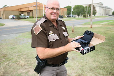 Staff photo by Harrison Grimwood Oklahoma Highway Patrol Lt. Mike Childress inspects the fire- arm, a token of appreciation from several local businesses, after his background check cleared.