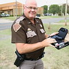 Staff photo by Harrison Grimwood<br /> Oklahoma Highway Patrol Lt. Mike Childress inspects the fire- arm, a token of appreciation from several local businesses, after his background check cleared.