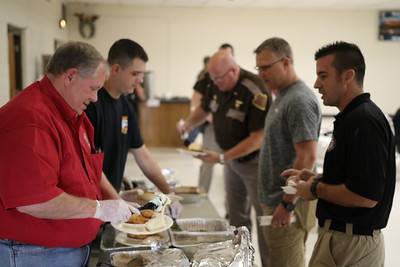 Staff photo by Harrison Grimwood Volunteers serve up food for local law enforcement — in and out of uniform — during a luncheon hosted by several local businesses.