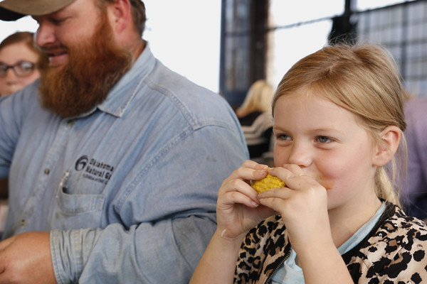 Staff photo by Harrison Grimwood<br /> Kaylee Wood, 7, chows down on sweet corn during the Ag Appreciation Dinner at the Love-Hatbox Sports Complex hangar.