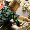 Staff photos by Harrison Grimwood<br /> Sharon DeLong, a member of Gore United Methodist Church, sets up part of the Charles Dickens' Christmas Village for display during the church's fund-raising sale.