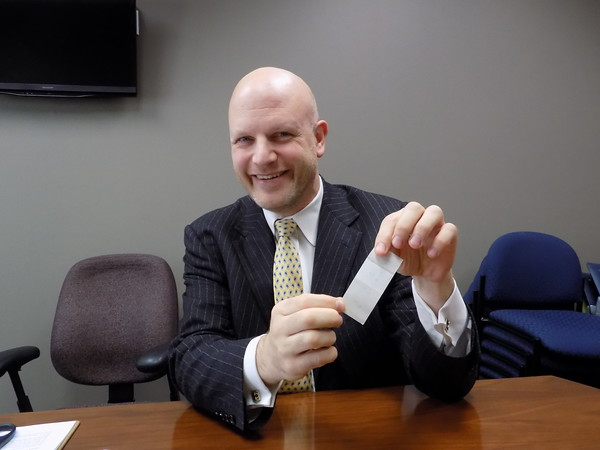 Special photo by Mike Elswick<br /> Dr. Joshua Garren holds a thin piece of vinyl used to help protect breast tissue during radiation treatment. The polyurethane sheet is placed on the women's breasts and protects the breast skin from friction and burns that have been a major side effect of radiation treatment in years past.