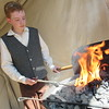 Staff photo by Cathy Spaulding<br /> Brendan Crotty heats a steel rod in a fiery forge in- side his blacksmithing tent. Crotty is among a couple dozen historical re-enactors at the Murrell Home An- tique Agriculture Festival this weekend.