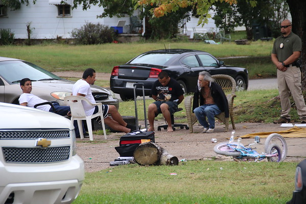Staff photo by Harrison Grimwood<br /> A Muskogee officer stands by with four suspects while other investigators search a residence during a Wednesday morning search warrant.