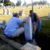 Special photo by Liz McMahan<br /> Keith Green, left, and Kenny Byrd of Muskogee Monument set a new tombstone Thursday morning at the grave of Henry Piquard in Wagoner's Elmwood Cemetery. Piquard, who died in 1919, has no known family in the area. His tombstone was destroyed about eight years ago when vandals went on a spree through the cemetery. Ron Ross, the cemetery's sexton, was bothered by Piquard's grave no longer being marked and spoke to the Muskogee firm about the cost of replacing it. He was going to pay for the replacement himself, but the monument company donated the new stone.