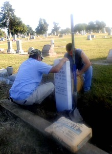 Special photo by Liz McMahan Keith Green, left, and Kenny Byrd of Muskogee Monument set a new tombstone Thursday morning at the grave of Henry Piquard in Wagoner's Elmwood Cemetery. Piquard, who died in 1919, has no known family in the area. His tombstone was destroyed about eight years ago when vandals went on a spree through the cemetery. Ron Ross, the cemetery's sexton, was bothered by Piquard's grave no longer being marked and spoke to the Muskogee firm about the cost of replacing it. He was going to pay for the replacement himself, but the monument company donated the new stone.