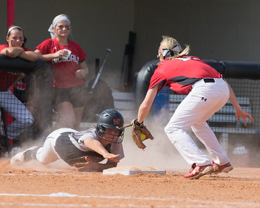 Special photo by Von Castor Wagoner's Madyson Robertson, left, over-slides third while Hilldale's McKenzie Plant waits to apply the tag Thursday afternoon in the 4A regional final at Lady Hornet Field.