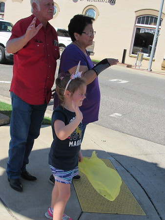 Bonnie Ragland, 4, joins Charlie and Ruth Reddin in waving to floats at the Fort Gibson Homecoming Parade.