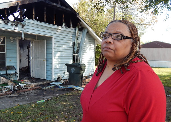 Staff photo by Wendy Burton<br /> Jo Ann Powell stands in front of her home, which burned early Monday, as she talks about her losses. Powell and her late husband, Richard,  built the home through Habitat for Humanity in 1995, and they were the first family in Muskogee to pay off their Habitat home.