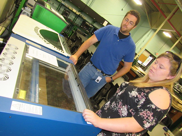 Staff photo by Cathy Spaulding<br /> New Fab Lab manager Nick Miller works with lab technician Lexi Whittle, a Muskogee High junior, on a laser engraver. Miller became manager earlier this month.